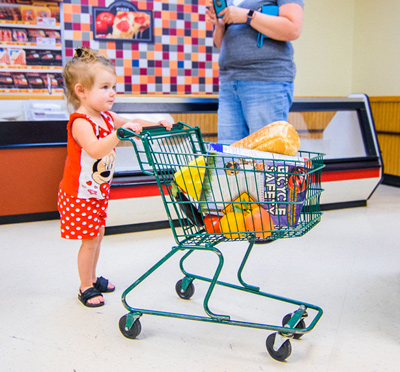 Young girl in Weis Market exhibit pushing shopping cart