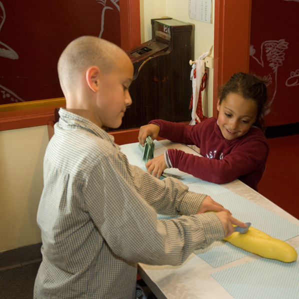 Two children interacting with cooking exhibit