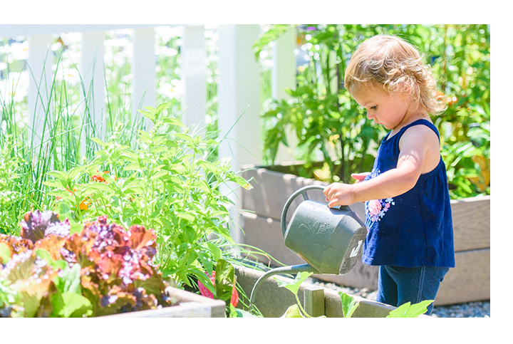Young girl watering garden outside