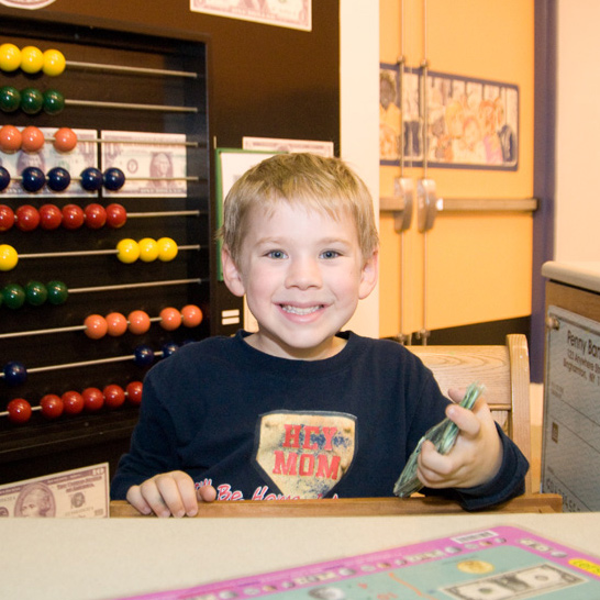 Smiling young boy playing with banking exhibit