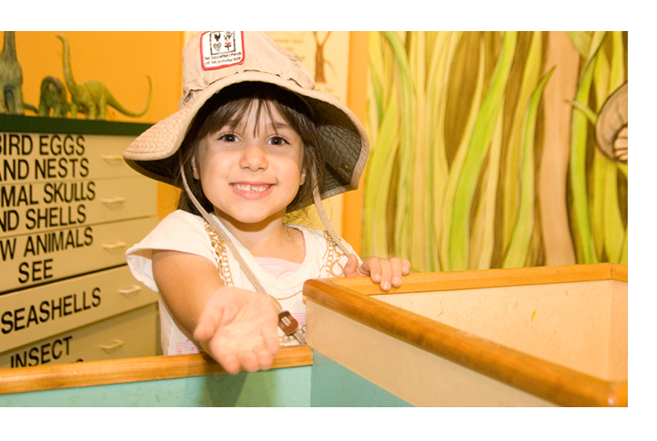 Young girl with her arm out smiling in safari exhibit