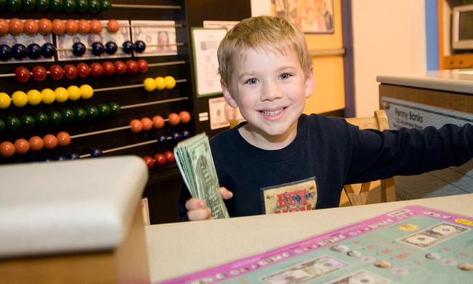 Boy playing at banking exhibit