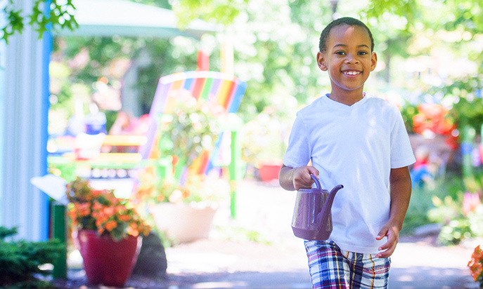 Young boy with watering can in Story Garden smiling